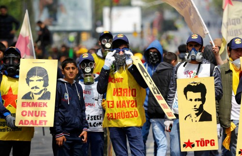 Protesters wear gas masks as they march with banners in Besiktas neighbourhood of Istanbul, Turkey, May 1, 2015. Turkish police used water cannon and tear gas on hundreds of stone-throwing protesters on Friday, a Reuters reporter at the scene said, after the demonstrators attempted to defy a ban and march on Taksim Square in central Istanbul. REUTERS/Murad Sezer